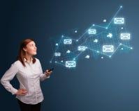 Jeune dame retenant un téléphone avec des flèches et des graphismes de message Photo stock