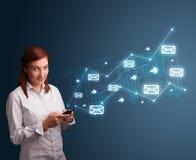 Jeune dame retenant un téléphone avec des flèches et des graphismes de message Images stock