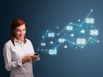 Jeune dame retenant un téléphone avec des flèches et des graphismes de message Photographie stock libre de droits