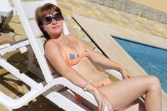 Jeune dame s'étendant sur la présidence de plage Photographie stock libre de droits