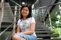 Jeune dame s'asseyant à l'escalier Photographie stock libre de droits