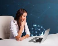Jeune dame s'asseyant au bureau et tapant sur l'ordinateur portable avec le netw social Photos stock