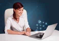 Jeune dame s'asseyant au bureau et tapant sur l'ordinateur portable avec le netw social Photographie stock