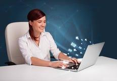 Jeune dame s'asseyant au DEST et tapant sur l'ordinateur portable avec l'ico de message Photos libres de droits