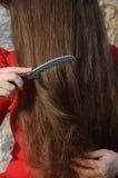 Jeune dame se peignant les beaux longs cheveux Photo stock