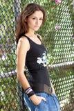 Jeune dame se penchant contre la frontière de sécurité Image stock
