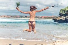 Jeune dame sexy dans le bikini sautant sur la plage avec le fruit sain cru frais d'ananas Concept heureux de vacances bali Photo libre de droits