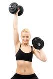 Jeune dame sportive établissant avec des poids Photographie stock libre de droits