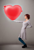 Jeune dame tenant le beau coeur du rouge 3d Photo stock