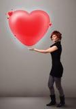 Jeune dame tenant le beau coeur du rouge 3d Photos stock