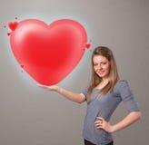 Jeune dame tenant le beau coeur du rouge 3d Photos libres de droits