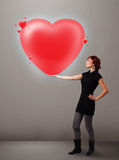 Jeune dame tenant le beau coeur du rouge 3d Photo libre de droits