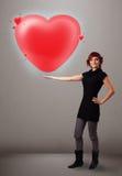Jeune dame tenant le beau coeur du rouge 3d Image libre de droits