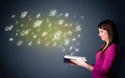 Jeune dame tenant le livre avec des lettres Photo stock