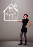 Jeune dame tenant une maison dessinée énorme photos libres de droits