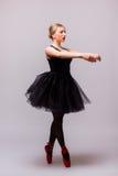 Jeune danse blonde de fille de ballerine et pose dans des chaussures noires de tutu et de ballet sur le fond gris Images libres de droits