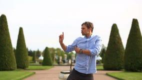 Jeune danse caucasienne drôle d'homme sur la pelouse d'herbe verte en parc le jour ensoleillé d'été banque de vidéos