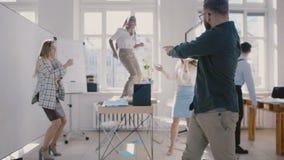 Jeune danse caucasienne heureuse de patron de société ainsi qu'avec des collègues, mouvement lent de célébration de succès  banque de vidéos