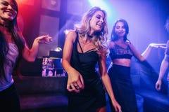 Jeune danse de clubber entourée par ses amis Photographie stock libre de droits
