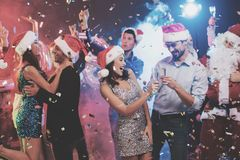 Jeune danse de couples avec des verres de champagne dans des mains Derrière eux danse leurs amis et homme habillés comme Santa Cl Photos libres de droits