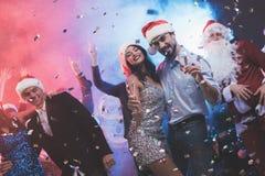 Jeune danse de couples avec des verres de champagne dans des mains Derrière eux danse leurs amis et homme habillés comme Santa Cl Images libres de droits