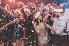 Jeune danse de couples avec des verres de champagne dans des mains Derrière eux danse leurs amis et homme habillés comme Santa Cl Images stock