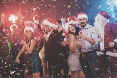 Jeune danse de couples avec des verres de champagne dans des mains Derrière eux danse leurs amis et homme habillés comme Santa Cl Image libre de droits