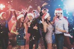 Jeune danse de couples avec des verres de champagne dans des mains Derrière eux danse leurs amis et homme habillés comme Santa Cl Photographie stock libre de droits