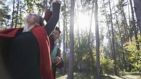Jeune danse de couples dans la forêt sur le fond de beaux pins Couples de danse interraciaux dans l'amour Le type est banque de vidéos