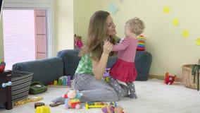 Jeune danse de jeu de mère avec la petite fille de bébé dans la chambre 4K banque de vidéos