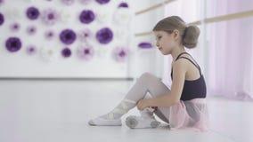 Jeune danseur classique attachant des chaussures de ballet avant la formation banque de vidéos