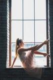 Jeune danseur posant à l'appareil-photo près de la fenêtre photographie stock