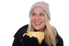Jeune de femme de boissons de thé et recherche tasse blonde Images stock