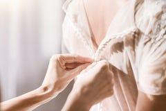 Jeune demoiselle d'honneur aidant la jeune mariée avec sa robe Image stock