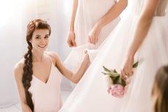 Jeune demoiselle d'honneur de sourire aidant la jeune mariée à être prête Photographie stock