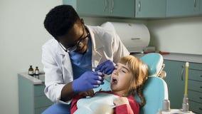 Jeune dentiste africain vérifiant les dents de peu de fille banque de vidéos