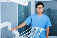 Jeune dentiste asiatique d'homme avec des outils de dentiste à la clinique Dentis Photos libres de droits