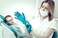 Jeune dentiste attentif mettant les gants bleus photos libres de droits