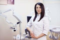 Jeune dentiste couverte de taches de rousseur de femme à son bureau Image stock