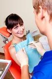 Jeune dentiste donnant une demande de règlement à son patient Images libres de droits