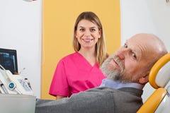 Jeune dentiste féminin avec le patient plus âgé images stock