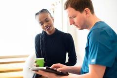 Jeune dentiste masculin montrant le rapport dentaire de rayon X sur le comprimé au beau patient féminin noir dans la clinique photographie stock