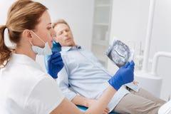 Jeune dentiste professionnel identifiant le diagnostic photographie stock