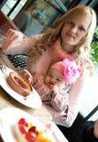 Jeune descendant de mère et de chéri prenant le petit déjeuner Image libre de droits