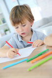 Jeune dessin heureux de garçon sur un papier Image libre de droits
