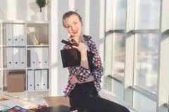 Jeune dessinateur d'intérieurs s'asseyant sur une table de travail souriant, regardant l'appareil-photo, tenant le carnet à dessi Photos libres de droits
