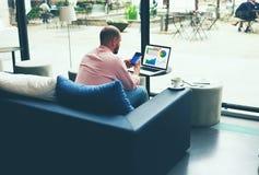 Jeune directeur beau d'une compagnie importante fonctionnant dans la pause de midi se reposant dans un café Image libre de droits