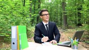 Jeune directeur complètement des idées travaillant sur le projet en parc vert, inspiré par nature photo libre de droits