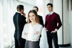 Jeune directeur féminin réussi devant son équipe dans le local commercial Photo libre de droits