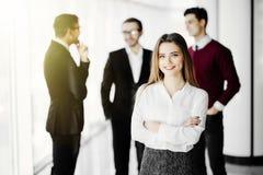 Jeune directeur féminin réussi devant son équipe dans le local commercial Images libres de droits
